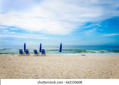 Tropical ocean beach with beach chairs and umbrellas. Scenic tourist destination location.  Relax and enjoy the warm white sand and sea water.