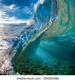 Tropical ocean with shorebreak. Surfing wave splashing on coral reef. Maldivian paradise with clouds on blue sky in daylight. View point from inside the wave