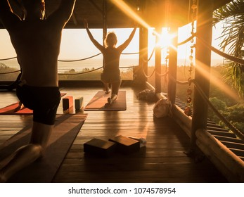 tropical open yoga studio place with people and a view outside to the ocean while sunset