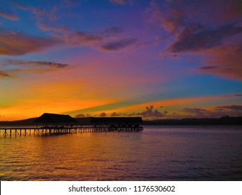 Tropical orange evening sunset and pier. Colorful sky in the dusk. Calm sea and cottage silhouettes above the water.