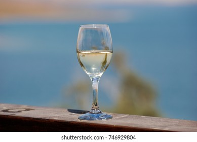 Tropical palm branches reflected in white wine glass on beach background