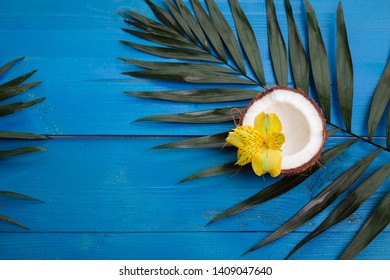 Tropical palm leaves, flowers, coconut on blue wooden background. Flat lay