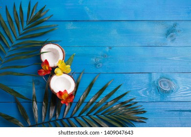 Tropical palm leaves, flowers, coconut on blue wooden background.