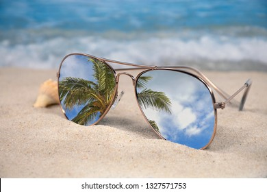 tropical palm tree reflection in aviator sunglasses with seashell in beach sand