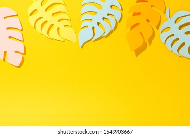 Tropical papercraft palm leaves on yellow background, space for text