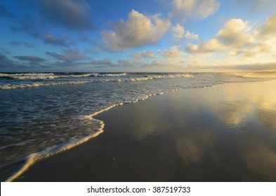 Tropical paradise beach with bright smooth mirror sand and crystal clear water during sunset