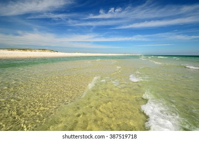 Tropical paradise beach with bright yellow sand and crystal clear green and cyan water