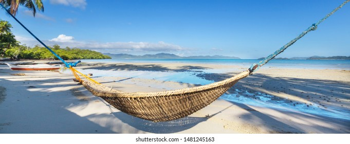 Tropical paradise beach with palm trees and traditional braided hammock