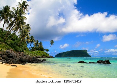 Tropical paradise seascpape, golden sandy beach with palm trees and pristine blue waters of Pacific Ocean, view from Upolu to Nu'utele island, Western Samoa, Polynesia