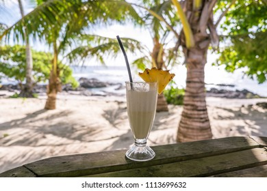 Tropical pina colada cocktail drink with pineapple garnish in glass with straw at exotic beach at Lefaga, Upolu Island, Western Samoa, South Pacific