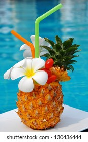 Tropical pineapple cocktail. Drink on the background of the pool.