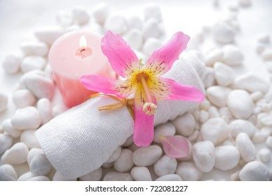 Tropical pink flower ,candle,rolled towel and pile of white stones background