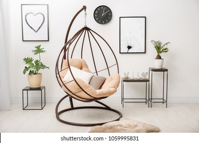 Tropical plants with green leaves and swing chair in room interior