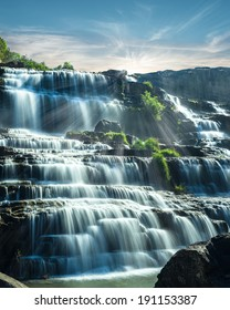 Tropical rain forest landscape with flowing blue water of Pongour waterfall at sunny day under blue sky. Da Lat, Vietnam