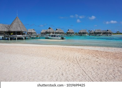 Tropical resort, beach sand with thatched bungalows over water in the lagoon, Tikehau atoll, Tuamotus, French Polynesia, Pacific ocean, Oceania