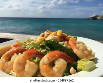Tropical salad with shrimps and papaya Caribbean food. Caribbean salad Summer food. Seafood platter Caribbean cuisine. Delicious healthy food background. Caribbean Seafood salad background