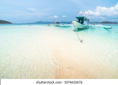 Tropical sandbar with tourists and boats on the Bulog Dos island, Palawan, Philippines