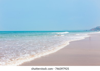 Tropical sandy beach, the sea with waves and the sunny sky. Summer paradise view of the ocean shore with a blue horizon. South Goa, India. Exotic rest, the concept of travel, lifestyle, adventure.