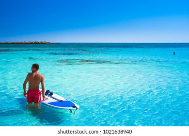 Tropical sandy beach with turquoise water, in Elafonisi, Crete, Greece. A young man with surf sup board on July 10,2017.