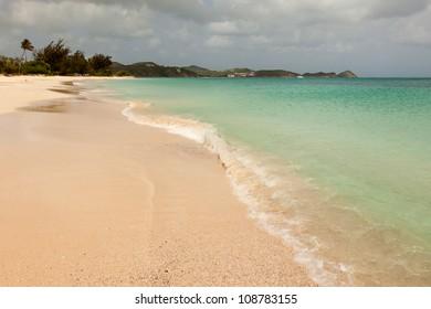 Tropical Sandy Caribbean Beach with Cloudy Overcast Sky Antigua