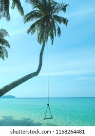 A tropical scene with blue ocean and a wooden swing hanging from a palm tree on Ko Kut island, Thailand