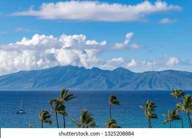 A tropical scene with an island across the ocean, a yacht in the water, and palm trees in the foreground. It is the Hawaiian island of Molokai, seen from Lahaina on Maui.