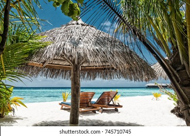 tropical scenery with two sunchairs on a white sandy beach