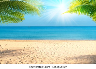 Tropical sea beach with sand, ocean, palm leaves and blue sky