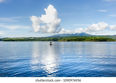 Tropical sea landscape , a little sailing  boat  , blue sky with white clouds reflection on the calm sea  , Papua New Guinea, Tufi