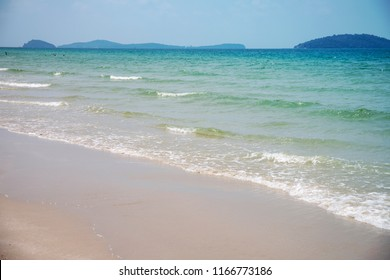 Tropical sea landscape with white sand and blue sea. Tropical seaside landscape with white sand beach. Beach day activity. Seashore view with distant island. Idyllic paradise vacation destination