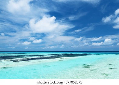 Tropical seascape of the fresh turquoise sea water, deep blue sky and white clouds in Maldives.