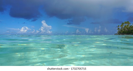 Tropical seascape, turquoise water of a lagoon with cloudy blue sky seen from water surface, French Polynesia, Pacific ocean, Oceania