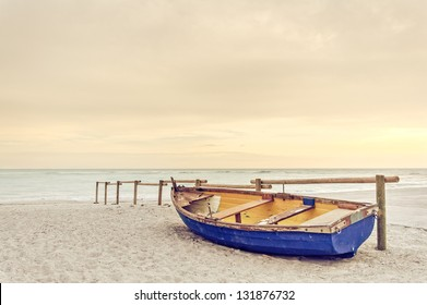 Tropical Seascape with a wooden, old and broken yellow blue boat on white beach on warm sunset.