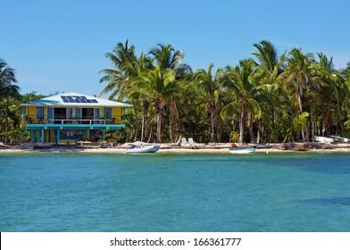 Tropical seashore with solar powered beach house and coconut trees, Caribbean, Bocas del Toro, Panama