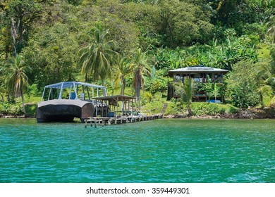 Tropical shore with an off-grid house and strange boat at dock on an island of the Caribbean coast of Panama, Bocas del Toro, Central America