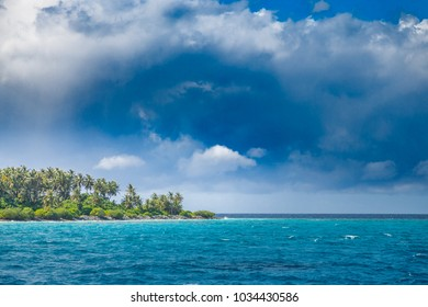 Tropical storm. Dramatic cloudscape with heavy rain and blue sea waves on the beach and tropical stormy weather at the horizon on the coastline of Maldives island.