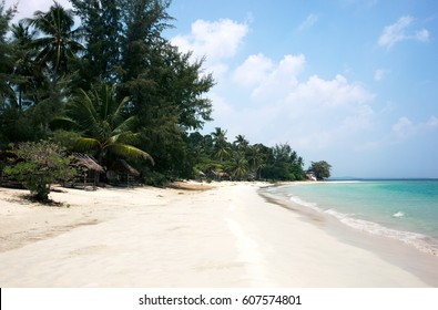 Tropical stretched out white sand beach and palm trees with blue colored ocean seashore water in the afternoon at Tanjung Pinang on Bintan island, Indonesia.