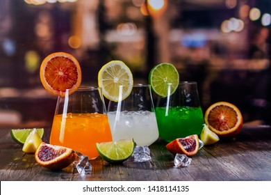 Tropical summer cocktails on a bar counter over restaurant lights background. Refreshing orange, white and green beverages. Copy space