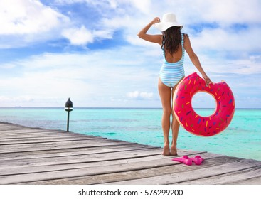 Tropical summer holiday concept, woman wearing hat and swimsuit standing on wooden pier by the beach