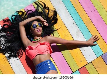 Modekonzept für tropische Sommerferien - Bräunungsfrau auf einem Holzsteg