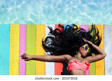 Tropical summer holiday fashion vogue concept - african american woman wearing sunglasses on a wooden pier background