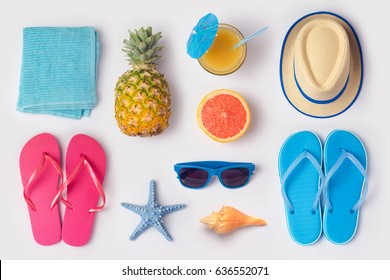 Tropical summer vacation concept with pineapple, juice and flip flops organized on white background. View from above. Flat lay - Shutterstock ID 636552071