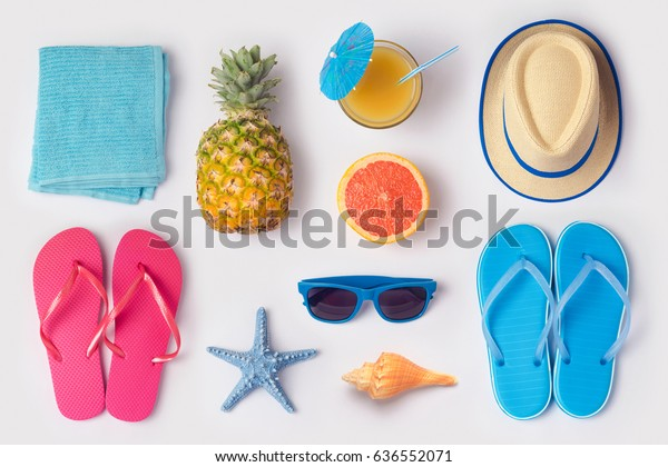 Tropical summer vacation concept with pineapple, juice and flip flops organized on white background. View from above. Flat lay