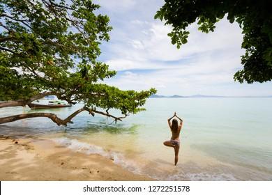 Tropical summer yoga session on beautiful sunrise beach, Koh Kradan island in Thailand. Vriksha asana - tree pose.