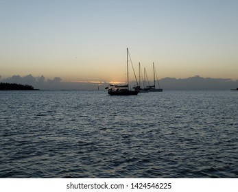 A Tropical Sunrise Seascape with yachts at anchor in the river mouth with calm seas at Bundaberg, Queensland, Australia.