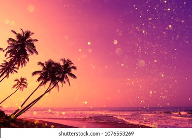 Tropical sunset beach with coconut palm trees silhouettes and magic shiny golden glitter effect