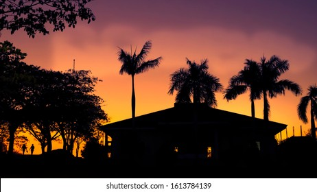 Tropical Sunset with palms, people and building silhouette in the Philippines.