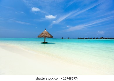 Tropical thatch umbrella on a beautiful beach at Maldives