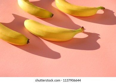 Tropical themed pattern of fresh bananas on a bright, colorful pastel pink background.