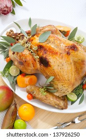 Tropical themed roasted turkey, garnished with cherry tomatoes, persimmos, and limes. Fresh tropical fruits, and flowers.